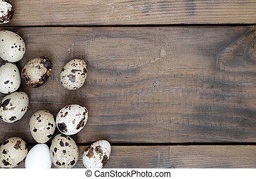 Quail eggs on a dark brown wooden surface, top view, empty place for text