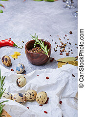 Quail eggs on a white fabric. A bowl of natural spices on a light background. Preparation, cuisine and cooking concept.