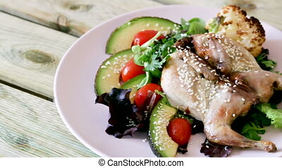Quail-tobacco with sesame and salad of avocado is tasty dish in the kitchen.