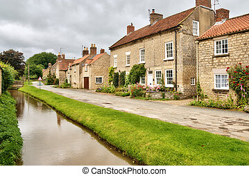 Quaint cottages and stream in an English village - A row of...