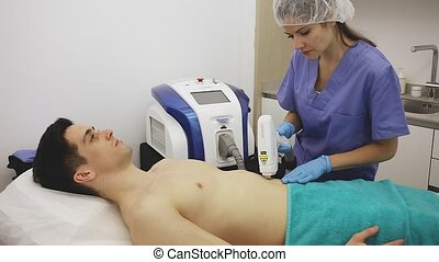 Young male client receiving hardware hair removal treatment on chest by professional cosmetologist in aesthetic clinic