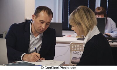Qualified and smart business person sitting near assistant in modern office room with loft interior working space. Man making notes and researching new startup or strategy project with woman