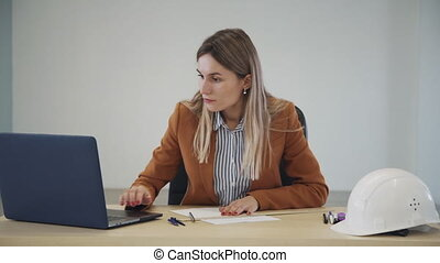 Qualified, skilled and ambitions person in formal wear clothes sitting behind table in modern work space office with bright interior. Architect woman using laptop and creating new project