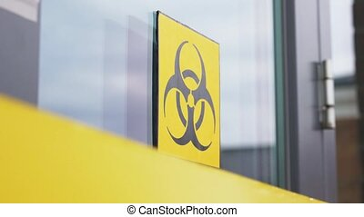 quarantine, contagion and pandemic concept - yellow biohazard sign on door