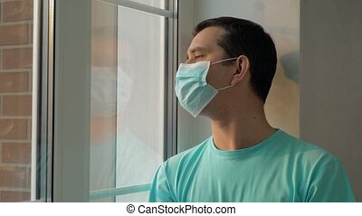 Coronavirus outbreak situation. Infected man on self-isolation looks at the street through the window of house. Man in a medical mask near the window. Man in surgical mask looking out his home window.