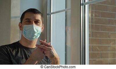 Concept home quarantine, prevention COVID-19. Forced Home Isolation. Sick man with mask is quarantined at home and looks out the window sadly. He cannot get out due to the COVID19 coronavirus pandemic