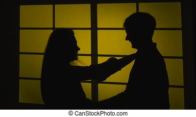 Quarrel in couple. Woman shakes a man. Silhouette. Slow motion. Close up