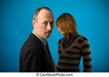 quarrel - senior man and young woman on blue background