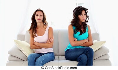 quarreling women - Sweet quarrelling women sitting on couch...