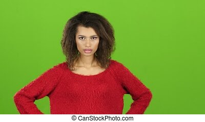 Quarrelsome african american woman swears looking at camera, green screen