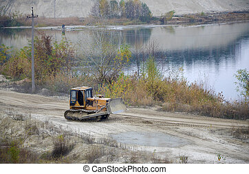 Quarry aggregate with heavy duty machinery. Caterpillar loader Excavator with backhoe driving to construction site quarry
