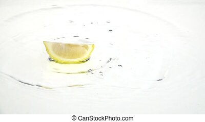 Quarter of a lemon drops into the water and remains there....