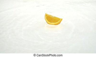 Quarter of a orange drops into the water and remains there....