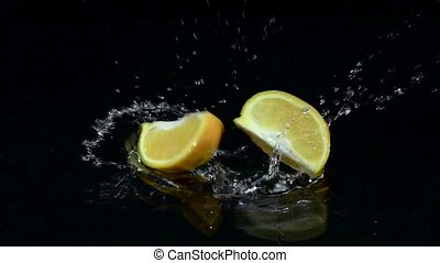 Quarter of orange falls into the water. Black background. Slow motion