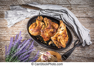 Quarters of fried chicken in a cast iron skillet.