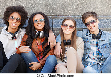 quatre, adolescent, séance, friends., gai, appareil photo, chaque, fin, sourire, amis, autre