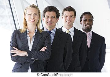 quatre, businesspeople, debout, dans, couloir, sourire