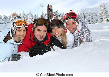 quatro, adultos jovens, deitando, em, a, neve