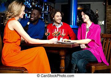 quatro, amigos, desfrutando, jantar, em, um, restaurante