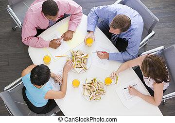 quatro, businesspeople, em, sala reuniões, tabela, com, sanduíches