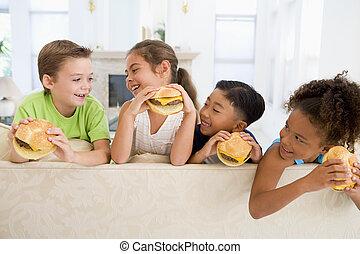 quatro, filhos jovens, comer, cheeseburgers, em, sala de estar, sorrindo