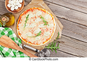 Quattro fromaggi pizza with lettuce on wooden table. Top view with copy space