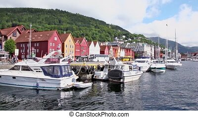Quay in dock with boats at coastal Bergen town, cars ride...