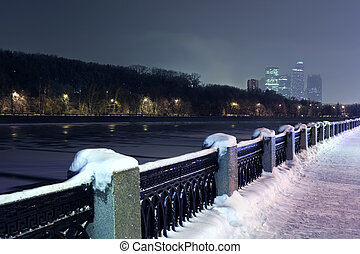 Quay of Moskva river and view of  Moscow City complex at night in winter
