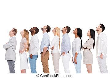 que, é, that?, vista lateral, de, positivo, diverso, grupo pessoas, em, esperto casual, desgaste, olhar, enquanto, ficar, uma fileira, e, contra, fundo branco
