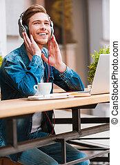 que, um, bonito, day!joyful, homem jovem, segurar passa, ligado, fones, enquanto, sentando, em, bar calçada