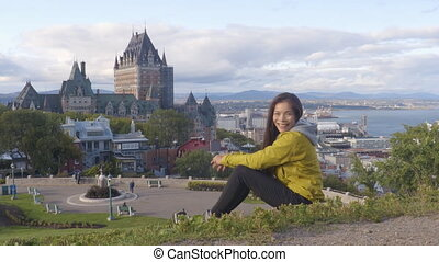 Quebec city Canada travel tourist enjoying view of Chateau Frontenac castle and St. Lawrence river in background. Autumn traveling holiday people. Looking at camera waving saying hello welcoming.
