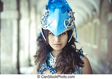 Queen, beautiful latin woman dressed in blue feather suit and helmet simulating an exotic bird in a place in autumn