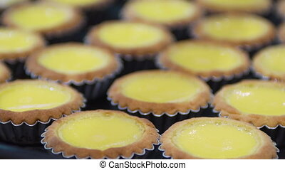 Medium low angle tilting shot of egg queen cakes arranged in a baking tray, street food market, Asia