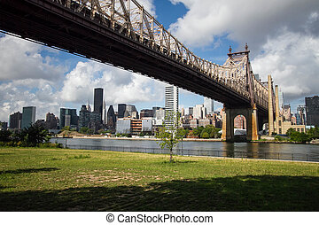Queensboro Bridge and Manhattan city with cloudy blue sky, New York