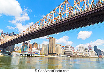Queensboro Bridge and Roosevelt Island Tramway over East River in New York city. A view from Roosevelt Island onto Lower East Side Manhattan with Queensboro Bridge and Tramway.