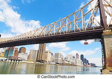 Queensboro Bridge and Roosevelt Island Tramway with view on Manhattan, New York. Manhattan skyscrapers and Queensboro Bridge in New York during in spring.