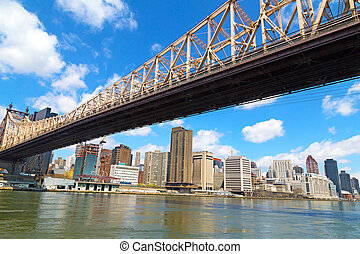 Queensboro Bridge and view on Manhattan from Roosevelt Island in spring. The bridge over East River in New York.