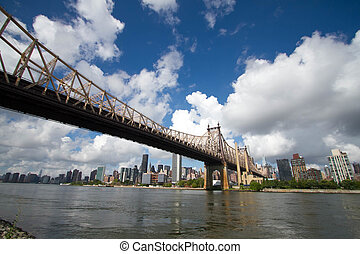 Queensboro bridge over the river and buildings in Manhattan with cloudy sky, New York