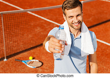Quench your thirst! Happy young man in polo shirt and towel on shoulders stretching out bottle with water while standing on tennis court