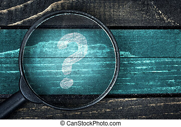 Question Mark painted and magnifying glass on table