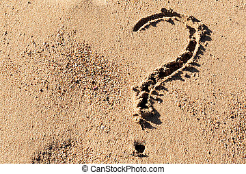 Question mark sign on sand beach near the sea