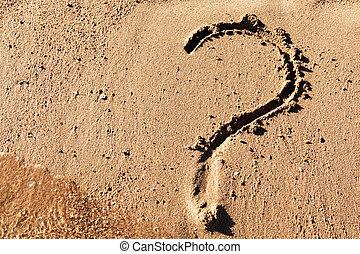 Question mark sign on sand beach near the sea.