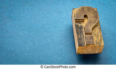 question mark - vintage letterpress printing block on blue handmade rag paper, question, doubt or uncertainty concept