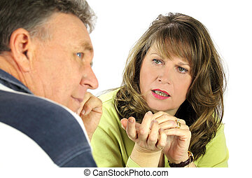 Man looking away while being questioned by his spouse.