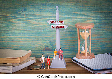 questions and answers. Signpost on wooden table