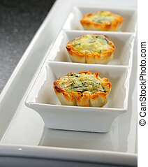 Small Individual Quiche Appetizers On A White Serving Dish