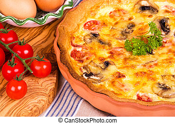 Homemade savory quiche in terracotta dish, with olive wood chopping board, cherry vine tomatoes and fresh eggs.