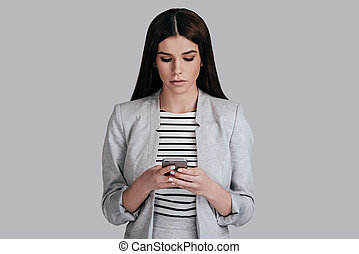 Quick business message. Beautiful young woman in smart...
