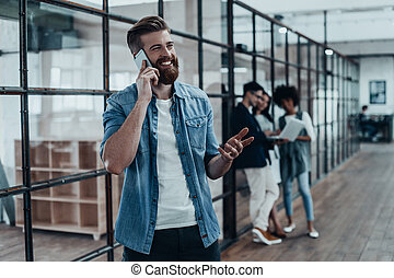 Quick business talk. Handsome young smiling man talking on the phone and gesturing while his colleagues standing in the background