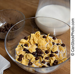Quick cereal breakfast. Corn flakes with chocolate balls and milk in a glass bowl on a wooden table with glass jug of milk and a bowl of chocolate balls on it. Healthy food concept